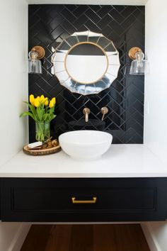 This powder room features a black tile wall with a round, decorative mirror serving as the main focal point. Farmhouse-style sconces provide ample light, and a basin-style sink in a floating counter adds classy simplicity.