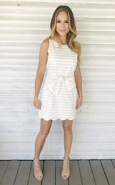With a tailored cut and a subtle beige hue, this sleeveless tie waist dress has a scalloped hem making it so elegant and the perfect pick for a wedding, shower, graduation and more. Fully Lined Model: