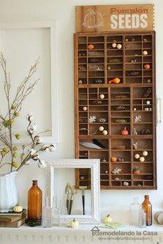 A printer's drawer is the backdrop for this pumpkin seeds Fall mantel.