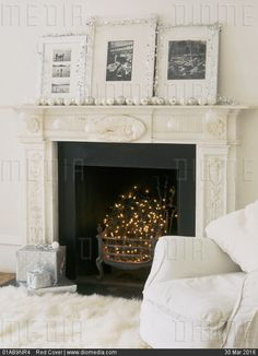 STOCK IMAGE - A detail of a traditional fireplace decorated for Christmas, black hearth with fairy lights, photographs trimmed with tinsel, silver and white baubles placed on the mantelpiece, presents, by www.DIOMEDIA.com
