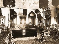 Queen Kapiolani kneels in the throne room where  King Kalakaua's body lies in state in 1891.