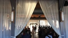 Fabric frames the ceremony while drapery filtered sunshine backlights the couple.  Marklet lights (9 rows) and drapery installation by Get Lit.  Venue: The Rickhouse