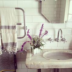 Slab sink, hex mirror, subway, & towel warmer