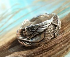 Sterling Silver Handmade Angel Wings Ring: A handful of feathery wings replicated in sterling silver are stacked, layered, and pressed into a pretty ethereal collage artisan ring. Flip it or spin it a