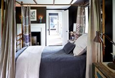 """Everybody says, 'I want to stay in that little brown bedroom,'"" says Ross. The bed is like the couchette of a train."" The bed's gold-leafed wood canopy and those earthy brown walls riff off the cool blue bedspread."