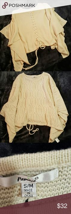 Cable knit sweater open sleeve Cream color cable knit sweater open sleeve, poncho style. Adorable lace up back. Asymmetric line at bottom. Like new! 21 inches long from top of shoulder to bottom. Papaya Sweaters Shrugs & Ponchos