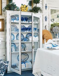 """""""Medium old"""" antique plates printed with a Blue Willow pattern are all part of the mix of dinnerware Sally displays with her linens in a glass-doored cabinet, which was made for a beloved uncle in China. He also purchased the 1940s blue stemware — at Woolworth's in downtown San Francisco."""