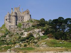 St. Michael's Mount, or, The Mount, in Cornwall, England.  It is surrounded by water and is accessible by a manmade pathway at low tide.
