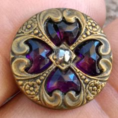Antique glass in metal button, rich purple faceted jewels in fancy brass setting, one tiny center cut steel OME
