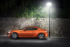 A 3d animation of a nice orange Toyota 86 next to a street light.