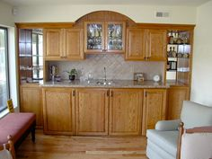 Wet bar made of wood with glass cabinets and granite countertop