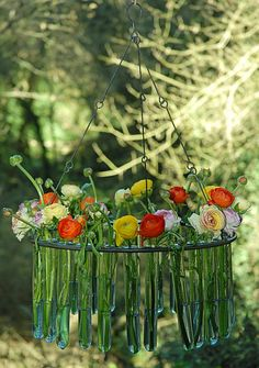 Test tube chandelier with colorful blooms hanging from trees.