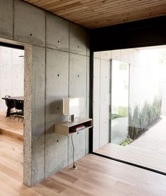 Modern Texas home with entryway with Tati lamp by Ferruccio Laviana and Kartell, white oak flooring, and concrete walls
