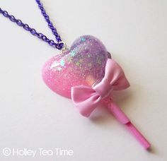 Sweet heart shaped lollipop made out of glittery resin. Ribbon is glued on to necklace. The lollipop stands about 3 inches tall. Necklace chain is a shiny purple. Chain is 20 inches long.  In the heart one side is pink glitter and on the other purple glitter,