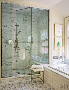 Works by Joan Miró brighten a bath, which features a Calacatta marble shower and Ann Sacks mosaic floor tile.
