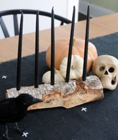 This candelabra idea can work both on a dining table as a centerpiece or to dress up a side table. Take a halved log and drill holes two inches apart along the top of it. Put black candles in the holes and place pumpkins, skulls, and a fake raven next to the candelabra to complete the vignette. When Halloween is over, you can replace the black candles and decorative objects with something more Thanksgiving- or holiday-appropriate.