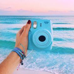 An aesthetic photo of a Polaroid camera at the beach