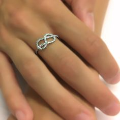 This beautiful infinity knot wedding band ring is crafted from 8mm wide 14k white gold and is also available in 14k yellow gold, set with fifty e...