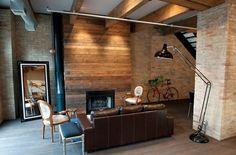 revêtement mural en bois et brique et un canapé en cuir marron dans le salon