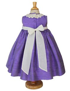 Ideal for weddings and pageants this exquisite girls silk dress in purple color and ivory smocking is adorned with an Ivory cotton lace collar. Ivory smocking on the empire waist line, feather stitch around the arm holes, covered back buttons, long organza sash in the back for a big bow. Fully lined.