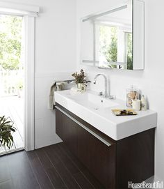 """My husband and I thought about two sinks, but we were about 10 inches short on space,"" says designer Lynn Butler Beling, who renovated the bath in her Southampton, New York, home. ""This sink and the countertop are all one piece — it's long enough that we can get ready at the same time, which seemed like a nice compromise. The sink and the vanity are made by Duravit, and I like how it's mounted on the wall. When you have limited space, the secret is to get things off the floor. The room…"