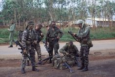An Australian Special Air Service (SAS) recon team getting ready to go out on patrol. A New Zealander pilot in background.