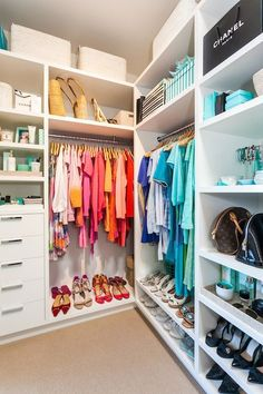 Lovely walk-in closet features white built in shelves stacked over a built-in dresser next to a handbag shelf and built-in clothes rod.