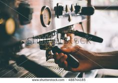 Barista holds a portafilter making coffee with a coffee machine. Toned picture