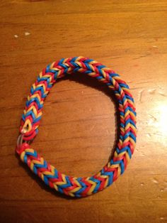 Triple single pattern fishtail bracelet using the Rainbow Loom.  Gold, red and blue.