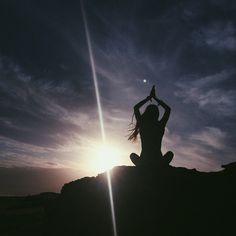 i like how she is doing a yoga pose and on a mountain