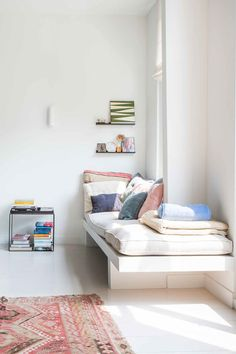 White modern day bed, pastel cushions, minimal