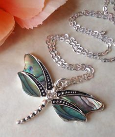 Dragonfly is a symbol of resurrection, hope, joy, and new beginnings. Abalone shell is known to aid in creativity and strengthens the heart by cleansing fear, sorrow and negative energies. This beautiful pendant necklace features a detailed vintage inspired silver dragonfly,