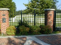 wrought iron fence w brick posts