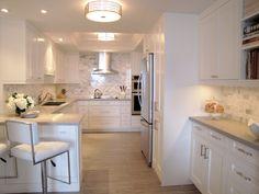 Shitake countertops and marbled backsplash give this elegant white kitchen by…