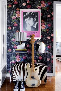 Guitar on console table in entryway with floral wallpaper.