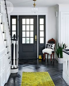 """This dark and demure entryway is the perfect place to say hello — or """"bye"""" — to guests. We love how the slate herringbone tile and black door contrast the white walls and staircase. Black Slate Floor, Black And White Tiles, White Walls, Black And White Hallway, Tiled Hallway, Tile Stairs, White Staircase, Staircase Design, Foyer Design"""