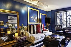 "Bold and Blue: The style of interior designer and 50 For 50 founder Noa Santos is modern and bold, and his living room is no different. The inspiration for it comes from several places. ""A stunning blue living room done by Todd Alexander Romano, his own, I believe; the pair of Hollywood Regency lamps on the living room credenza found at Green Flea this summer; and the bold striped rug from Housing Works.""  Source: Francisco Aguila"