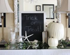 EasyCoastal Halloween decorations in white: white pumpkins, white seashells, white hurricane candles in sand. Halloween Harbor ~~ Halloween by the Sea Party Decorations & Ideas