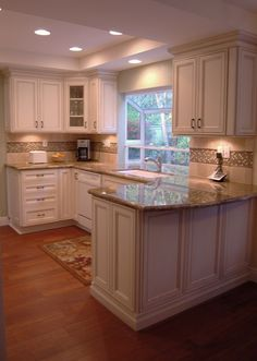 White cabinets and beige granite tops. No to the backsplash