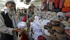 Afghan man checks a skull cap before buying it ahead of Eid-al-Fitr in Kabul