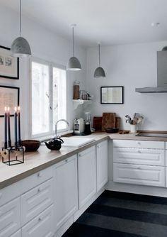 #Cuisine avec sol gris foncé, meubles blancs, murs blancs et plan de travail bois clair. Les tableaux et les luminaires tombant apportent un petit plus