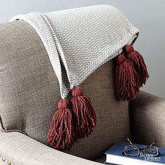 Glam-up a blanket with show-off tassels in seasonal hues. This cozy craft is easy enough to switch out with each change in the weather.