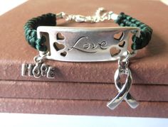 "Green Satin Cord is macramed onto both sides of an Antique Silver ""Love"" Bracelet Bar.  ""Hope"" Charm and Silver-colored Awareness Ribbon Charm are attached. www.etsy.com/shop/jewelrydesigned4you"