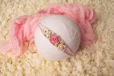 This beautiful newborn tieback features a medium pink rose with an off white rose on each side. Behind the flowers rests crocheted mohair lace weave with sewn on pearls. Band is stretchy.