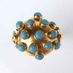 Yellow gold turquoise ring, tests high carat. Yellow gold turquoise ring, tests high carat. The domed surface of the ring set with thirteen turquoise cabochons to open work, wreath set shoulders. Ring size N. Weight 3.7 grams.