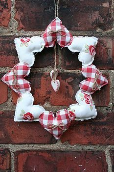 cloth material, cut into heart shapes..use twine or string to add wood shaped hearts in middle. use ribbon as a hanger. sew together with cotton in middle of hearts.