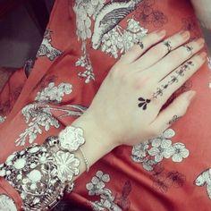 Henna hands with boho silver bracelets.