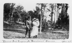 Sharing Brentwood, Ruahine Street; Captain and Mrs Brocks with son Basil; daisies and lagoon in grounds. [P2-846-1990] at Upper Hutt City Library. Captain Arthur William Brocks was a British Army officer who was brought over by the New Zealand Defence Department to serve as a bayonet-fighting and physical training instructor at Trentham Camp.