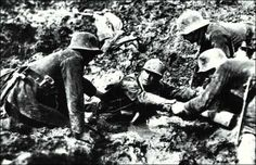 German soldiers rescue a French soldier from a shell hole that was filled with treacherous mud.