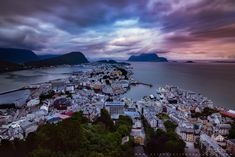 https://flic.kr/p/27uKZwG | The moody Ålesund in Norway | www.aziznasutiphotography.com                    Ålesund is a port town on the west coast of Norway, at the entrance to the Geirangerfjord. It's known for the art nouveau architectural style in which most of the town was rebuilt after a fire in 1904, as documented at the Jugendstilsenteret museum. There are panoramic views of Ålesund's architecture, the surrounding archipelago and fjords from the Mount Aksla lookout.